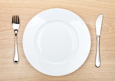 Empty white plate with silverware on wooden table Royalty Free Stock Images