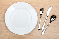 Empty white plate with silverware on wooden table Stock Photo
