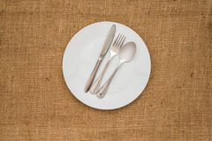 Empty white plate and  spoon, fork, knife Stock Image