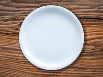 Empty White Plate On Table. An Empty White Plate On A Rustic Wooden Table Royalty Free Stock Image