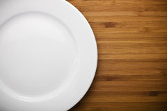 Empty white plate on wood Stock Image