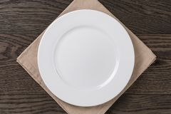 Empty white plate on wood table with napkin. Top view Royalty Free Stock Images