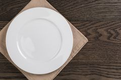 Empty white plate on wood table with napkin Stock Images