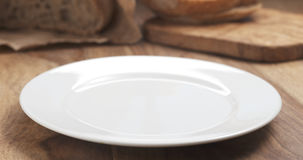 Empty white plate on wood table for your dish. 4k photo Royalty Free Stock Images