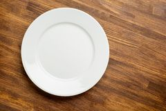 Empty white plate on wooden background top view Royalty Free Stock Images