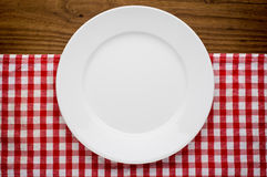 Empty white plate on wooden over red grunge