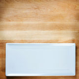 Empty white plate on wooden table Stock Images