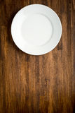 Empty white plate on wooden table Royalty Free Stock Photos