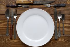 Empty white plate on wooden table close up. Nearby are a variety of old Cutlery, knives, forks and spoons. The theme of food, stock photo