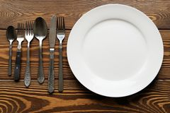 Empty white plate on wooden table close up. Nearby are a variety of old Cutlery, knives, forks and spoons. The theme of food, royalty free stock photography