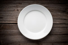 Empty white plate on wooden table Stock Image