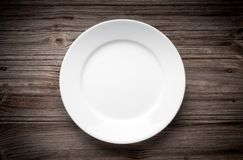 Empty white plate on wooden table Stock Photography