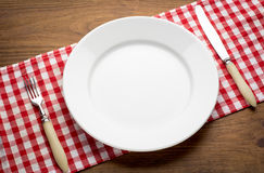 Empty white plate on wooden table over red grunge
