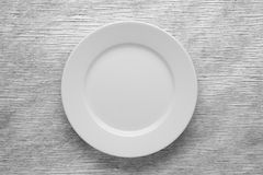 Empty white plate on wooden table. Top view Stock Photos