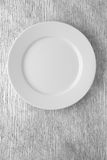 Empty white plate on wooden table. Top view Stock Image