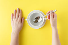 Empty white plate on yellow background with hands and spoon. Sou Royalty Free Stock Images