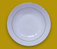 Empty white plate on a yellow table.View from above Royalty Free Stock Photos