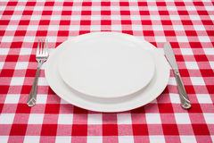 Empty white plates on checkered tablecloth Stock Photos