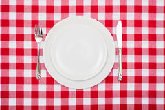 Empty white plates on checkered tablecloth Royalty Free Stock Images
