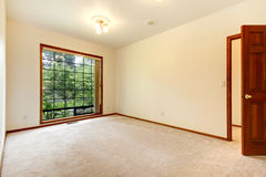 Empty white room with wood door and beige carpet. Royalty Free Stock Image
