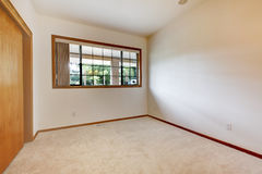 Empty white room with wood door and beige carpet. Royalty Free Stock Photography