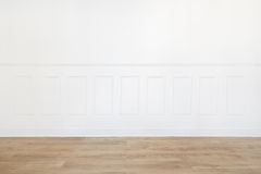 Empty white room with wooden floor and wood trimmed wall Royalty Free Stock Image