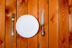 Empty white round plate with antique knife and fork on wooden background. Top View with text space. Stock Photo