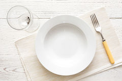 Empty white round soup or pasta plate with fork and glass. On white wood from above. stock images
