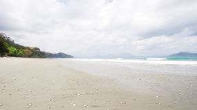 Empty white sand beach and clear blue ocean waves. Empty white sand beach and clear blue ocean waves at Bajawa Ruting Flores in the morning Stock Images