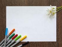 Empty white sheet of paper for text on a dark wood background. Around it are colored felt-tip pens and flowers. Mockup. Empty white sheet of paper for text on a royalty free stock photos