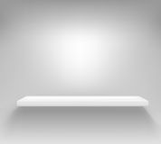 Empty white shelf hanging on a wall Royalty Free Stock Images