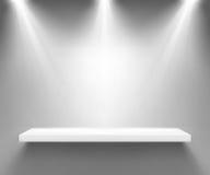 Empty white shelf illuminated by three spotlights Royalty Free Stock Image