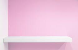Empty white shop shelf, retail shelf on pink vintage background. stock images