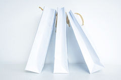 Empty white shopping bag with gold rope hanking isolated on whit Royalty Free Stock Photo
