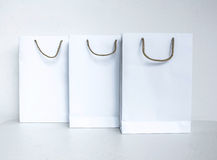 Empty white shopping bag with gray rope hanking isolated on whit Royalty Free Stock Photography