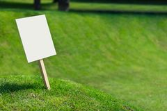 Empty white sign board on a small hill with freshly cut green grass stock photo