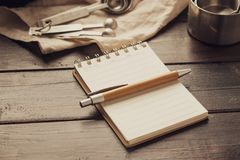 Empty white space notebook with pen and pastry bakery tools on wooden background royalty free stock photo