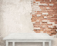 Empty white table next to brick wall.  stock images