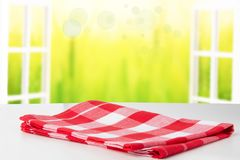 Empty white table top with red checkered napkin or tablecloth on. View through a opened window into an abstract light autumn landscape. Space for your food and royalty free stock photos