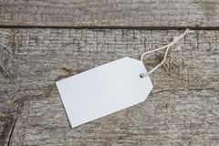 Empty white tag on old wooden background. Discounts and sales Stock Image
