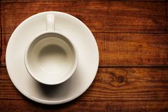 Empty white teacup and saucer on old wood texture background royalty free stock photos