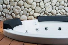 Empty white whirlpool bathtub with stone wall background. Empty white whirlpool bathtub on wooden floor with stone wall background Royalty Free Stock Photo