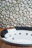 Empty white whirlpool bathtub on wooden floor with stone wall. Empty white whirlpool bathtub on red wooden floor with stone wall background Stock Photo