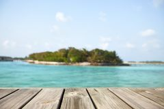 Empty white wood surface over blur blue ocean lagoon and sky and tropical for product placement and display. Royalty Free Stock Photo