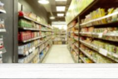 Empty white wood table supermarket blurry for background. Empty white wood table blurry supermarket convenience store product shelf for background stock photo