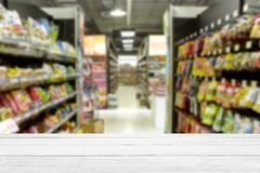 Empty white wood table supermarket blurry for background. Empty white wood table blurry supermarket convenience store product shelf for background royalty free stock photos