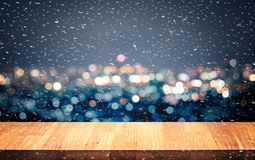 Empty of white wood table top on blur night town,cityscape backgrounds. And snowy.For montage product display or key visual layout royalty free stock photos