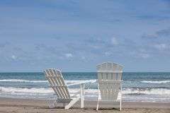Empty white wooden chairs at a paradisiac beach on the tropics in a beautiful sunny day. In Cartagena de Indias royalty free stock image