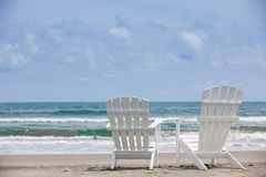 Empty white wooden chairs at a paradisiac beach on the tropics in a beautiful sunny day. In Cartagena de Indias royalty free stock images