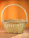 Empty wicker basket. On a orange background Royalty Free Stock Images